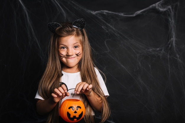 Funny girl with cat ears and trick or treat bucket Free Photo