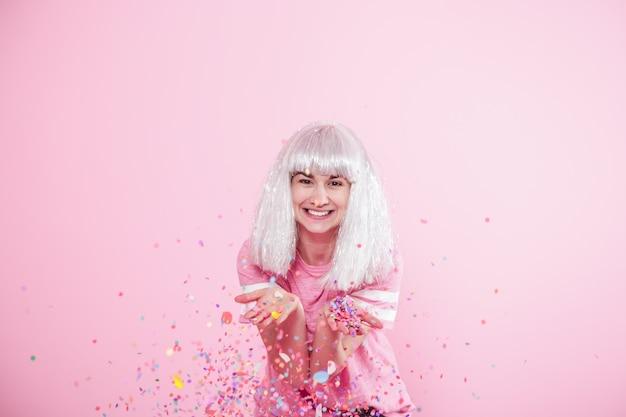 銀髪の面白い女の子は、ピンクの背景に笑顔と感情を与えます。若い女性または紙吹雪の十代の少女 無料写真