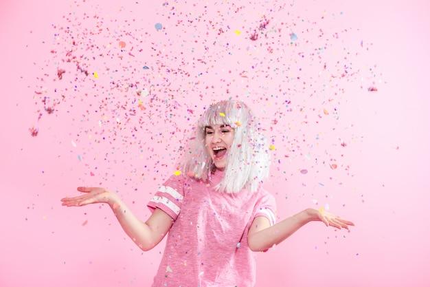 Смешная девчонка с серебряными волосами дарит улыбку и эмоции на розовой стене. молодая женщина или девушка с конфетти Premium Фотографии