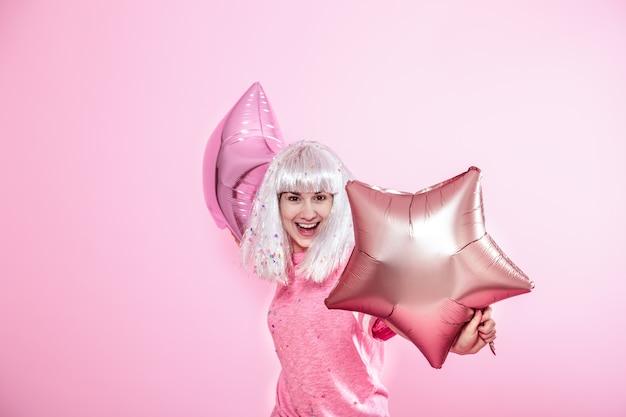 Смешная девчонка с серебряными волосами дарит улыбку и эмоции. молодая женщина или девушка с воздушными шарами и конфетти Premium Фотографии