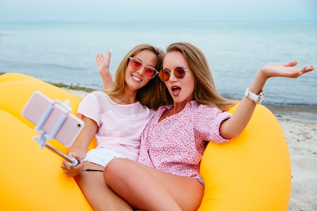 Funny girls posing at camera while taking a selfie on smartphone, sitting on air sofa lamzac Free Photo