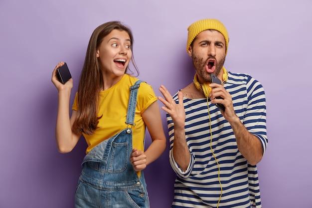 面白い男は好きな歌を歌い、マイクのように携帯電話を口の近くに持ち、明るい女性は近くで踊り、パーティーで楽しんで、おしゃれな服を着て、幸せな表情をしています 無料写真