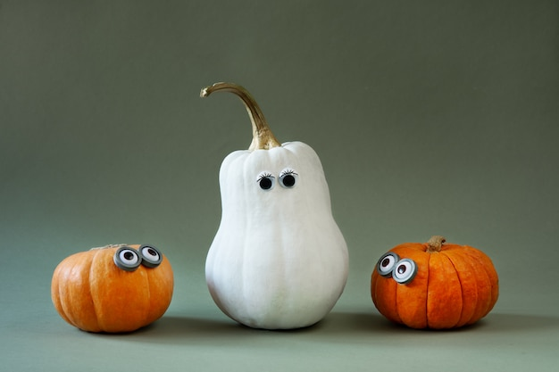 Funny halloween pumpkins with googly eyes on green Premium Photo