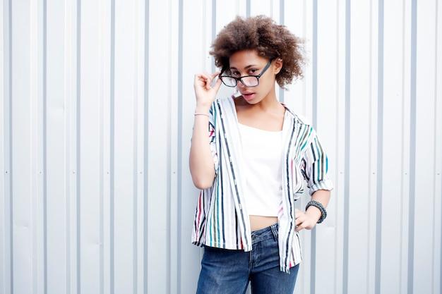 Смешная счастливая черная афро женщина в белой футболке и джинсах Premium Фотографии