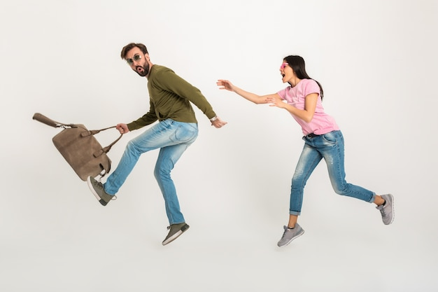 Смешная счастливая пара прыгает изолированно, симпатичная улыбающаяся женщина в розовой футболке бежит за мужчиной в толстовке, держащим дорожную сумку, одетую в джинсы Бесплатные Фотографии