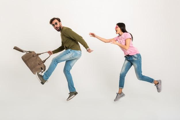 Coppie felici divertenti che saltano donna isolata, abbastanza sorridente in maglietta rosa che corre dietro l'uomo in borsa da viaggio della holding della felpa, vestita in jeans Foto Gratuite