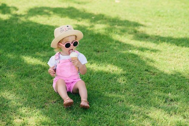 Смешная счастливая девушка малыша нося розовые комбинезоны лета, шляпу и розовые солнечные очки сидит на зеленой лужайке ест ванильное белое мороженое в солнечном саде. Premium Фотографии