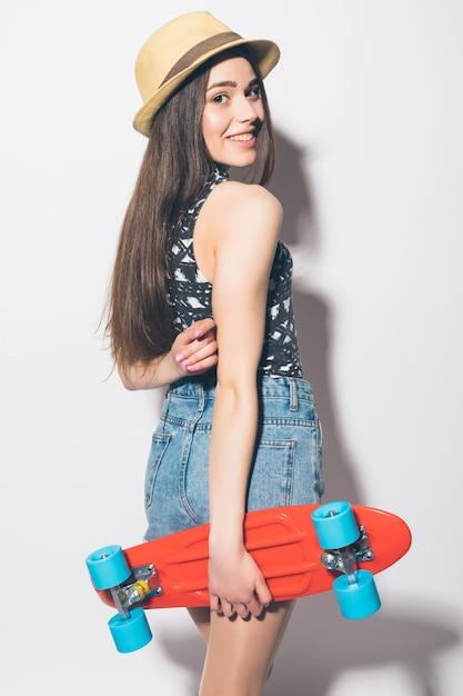 Donna divertente hipster con longboard rosa isolato Foto Gratuite