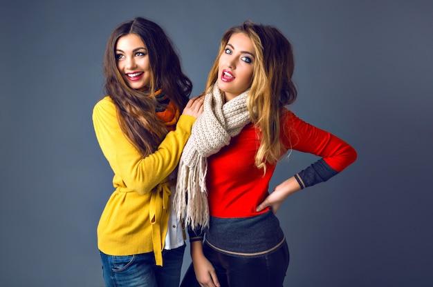 クラシックなカシミヤのセーターとスカーフを身に着けている、スタジオで楽しんでいる流行に敏感な女の子の面白い屋内ポートレート 無料写真