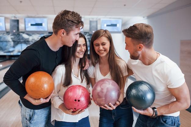 Scherzo divertente. i giovani amici allegri si divertono al bowling durante i fine settimana Foto Gratuite