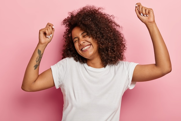 Funny joyous woman raises arms and dances carefree, feels pleasure and amused, laughs happily, eyes closed from satisfaction, moves along with music, has tattoo dressed in casual wear isolated on pink Free Photo