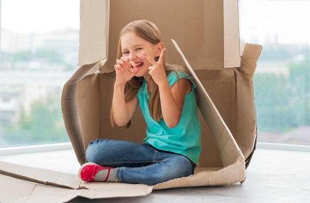 それをプレイハウスとして使用して段ボール箱に座ってジェスチャーをしている面白い子供の女の子 Premium写真
