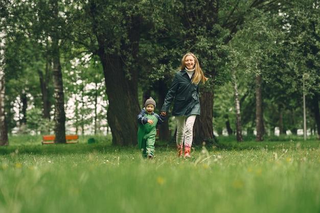 Забавный малыш в сапогах, играющих в парке дождя Бесплатные Фотографии