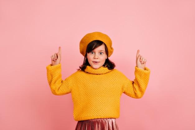 재밌는 꼬마. 분홍색 벽에 위로 손을 포즈 작은 프랑스 소녀. 무료 사진