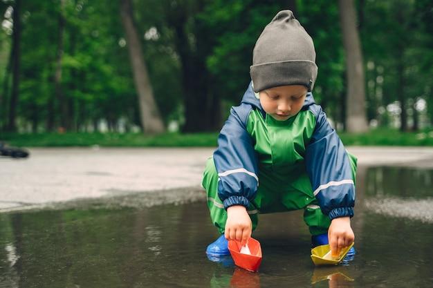 Bambino divertente in stivali da pioggia che giocano in un parco di pioggia Foto Gratuite