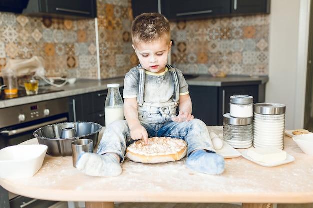 小麦粉で遊んでケーキを味わう素朴なキッチンのキッチンテーブルの上に座って面白い子供。 無料写真