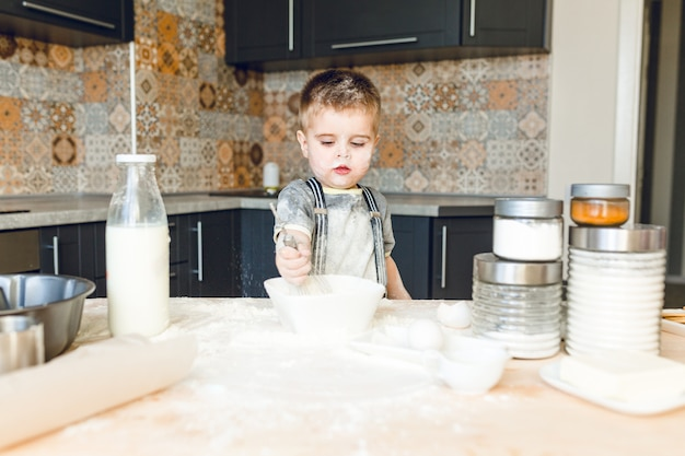 小麦粉で遊ぶラスティックキッチンに立っている面白い子供。彼は小麦粉で覆われていて、面白そうです。 無料写真
