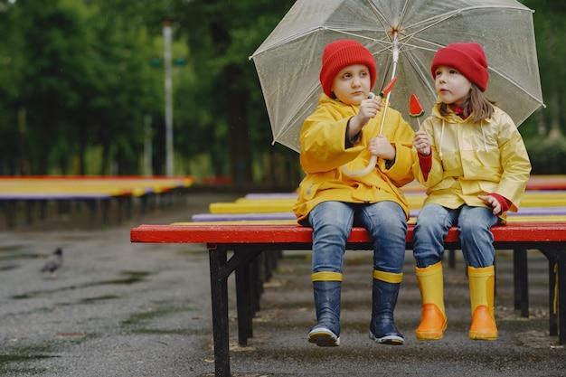 Веселые дети в дождевых сапогах играют в дождливом парке Бесплатные Фотографии