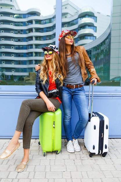 旅行の前に楽しんで、空港の近くで荷物を持ってポーズをとり、明るくカジュアルなスポーティーな服とサングラスを身に着けて、新しい感情の準備ができているかなり親友の女の子の面白いライフスタイルの肖像画 無料写真