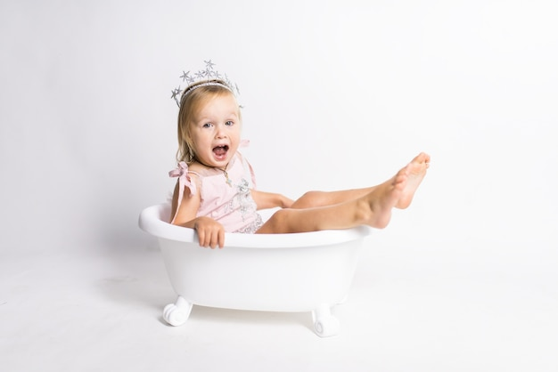 Funny little blonde girl sits in a bath in the studio Free Photo