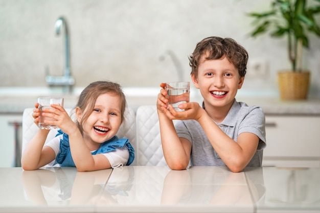 Funny little children drink water in the kitchen at home Premium Photo