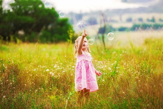 Funny little girl catching soap bubbles in the summer on nature. happy childhood concept Premium Photo