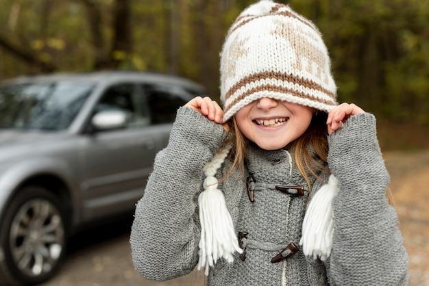 Funny little girl covering her face with winter hat Free Photo