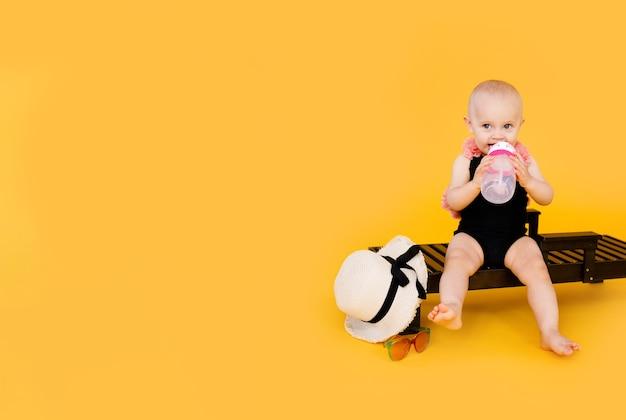Смешная маленькая девочка, одетая в черно-розовый купальник, большая шляпа, сидит на деревянном шезлонге с бутылкой воды на желтом Premium Фотографии
