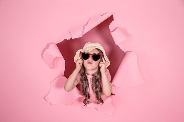 재미 있은 어린 소녀 해변 모자에 구멍에서 엿보기와 컬러 배경에 하트 모양의 안경, 텍스트 장소, 스튜디오 촬영 무료 사진