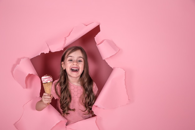 Funny little girl with ice cream on colored background Free Photo