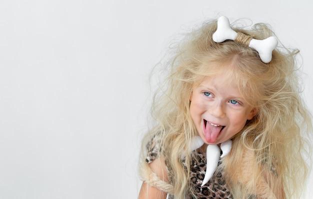 원시인 의상에서 혀와 털이 많은 머리카락을 가진 재미있는 어린 소녀 프리미엄 사진