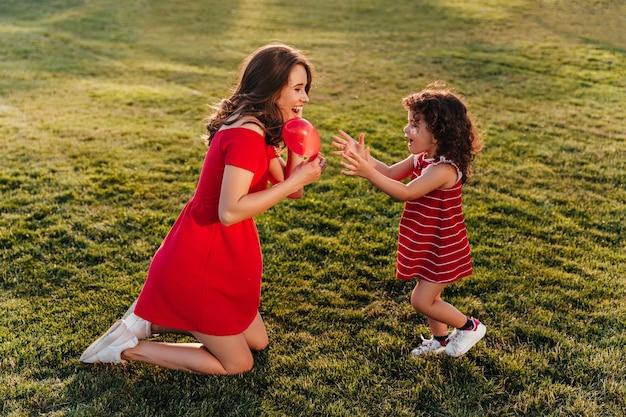 お母さんと夏の日を楽しんで赤いドレスを着た面白い小さな子供。草の上で娘と遊ぶゴージャスなブルネットの女性の屋外写真。 無料写真