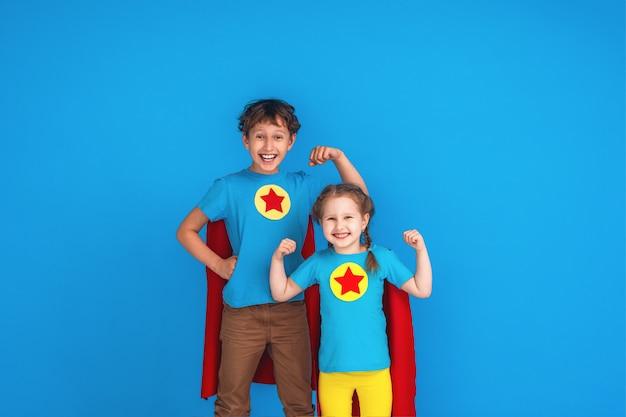 Смешные маленькие дети супер герой питания в красных плащах и маске. Premium Фотографии