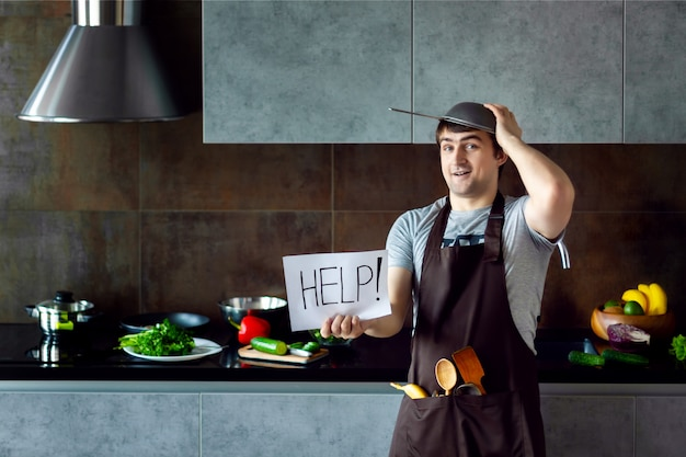 金属ふるい、フライパン、木製の台所用品、エプロンを調理しようとするとおかしな敗者の男性男性が失敗し、灰色のモダンなロフトキッチンで助けが必要です。キッチンのコンセプトに失敗した学士。 Premium写真