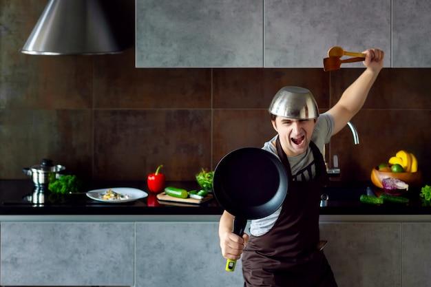 Забавный мужчина-неудачник с металлической кастрюлей на головной сковороде и деревянной кухонной утварью в позе ниндзя, пытающейся приготовить, провалился и закричал на серой современной кухне-лофте. неудачный бакалавр по концепции кухни Premium Фотографии