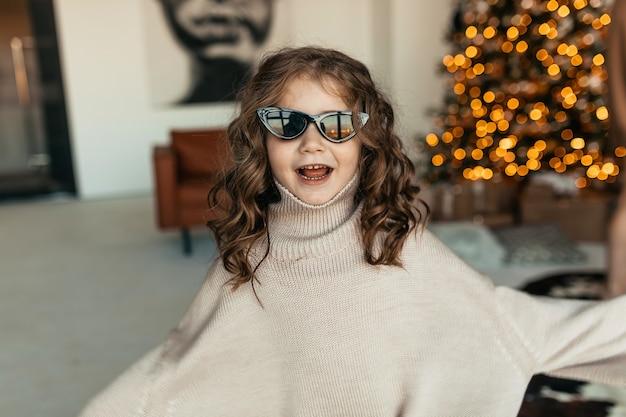 크리스마스 트리 앞에서 춤을 추는 특대 니트 스웨터와 선글라스를 착용하고 곱슬 머리를 가진 재미 있고 사랑스러운 어린 소녀 무료 사진