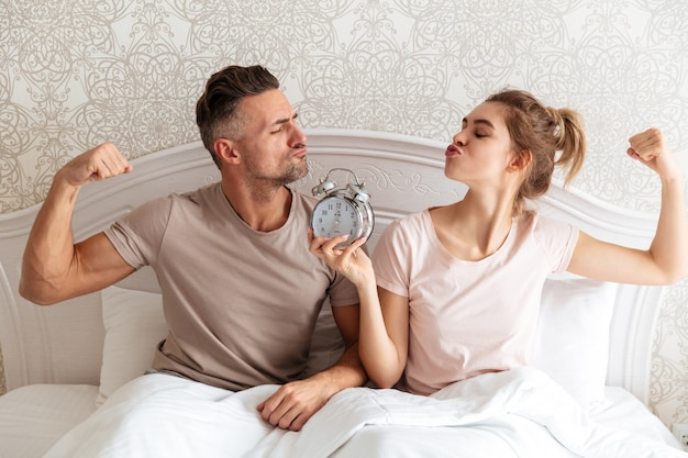 Funny lovely couple sitting together on bed with alarm clock Free Photo