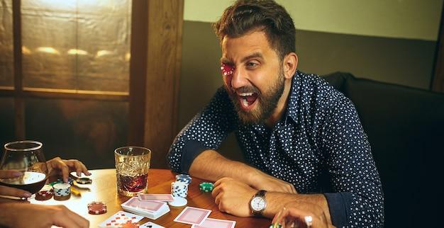 Amici divertenti maschii e femminili che si siedono alla tavola di legno. uomini e donne che giocano a carte. mani con il primo piano dell'alcool. Foto Gratuite