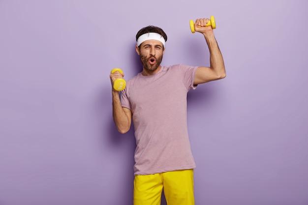 おかしな男は楽しい、ダンベルを使ったエクササイズ、アクティブな服を着て、健康的なライフスタイルに動機付けられ、朝に定期的なトレーニングを受けています 無料写真