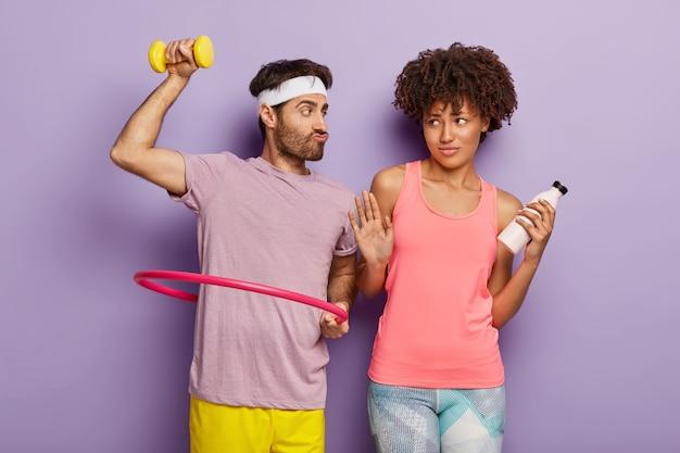 L'uomo divertente solleva il manubrio, posa con l'hula hoop, suggerisce alla ragazza di provare aerobica, la donna dalla pelle scura fa il gesto di rifiuto, tiene la bottiglia con acqua fresca. una coppia di razza mista va a fare sport insieme Foto Gratuite