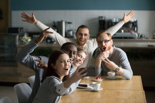 Funny millennial friends taking group selfie on smartphone in cafe Free Photo