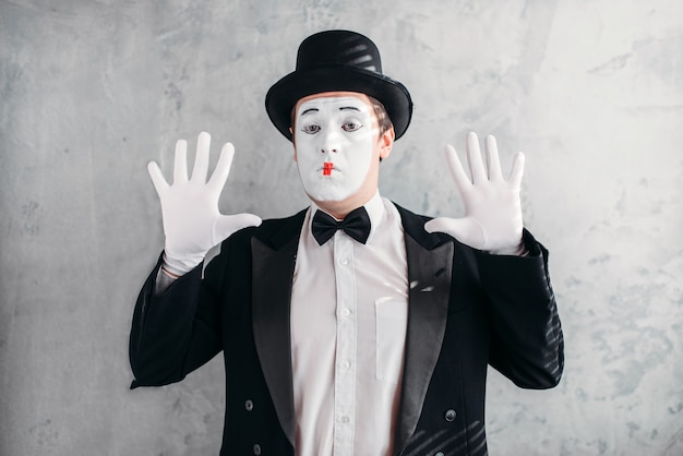 Funny mime actor with makeup mask. pantomime in suit, gloves and hat. Premium Photo