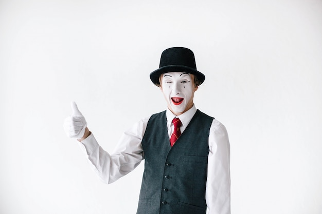 Funny mime in black hat holds his thumb up Free Photo