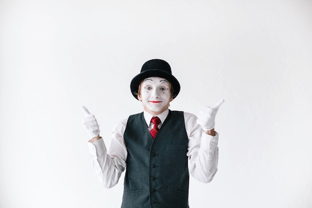 Funny mime in black hat holds his thumbs up Free Photo