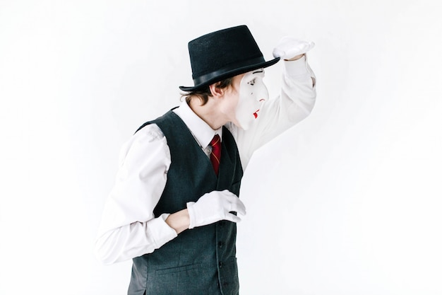 Funny mime in black hat looks far way on white background Free Photo
