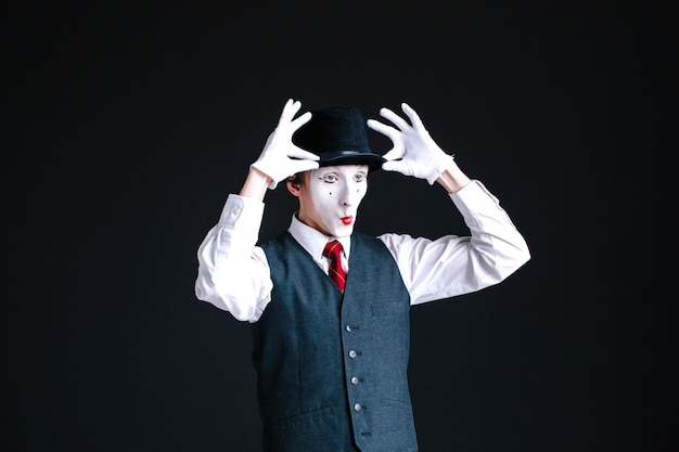 Funny mime fixes his hat Free Photo