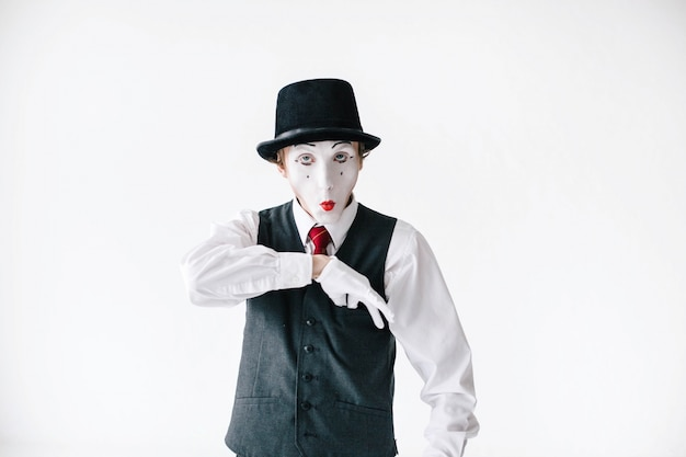 Funny mime takes something from pocket on his waistcoat Free Photo