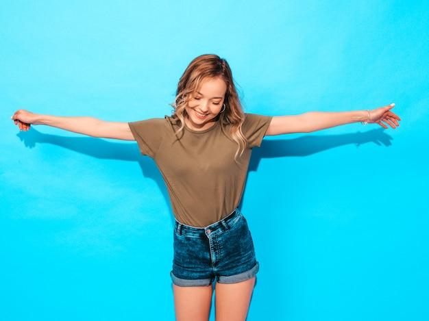 Funny model posing near blue wall in studio.raises her hands Free Photo