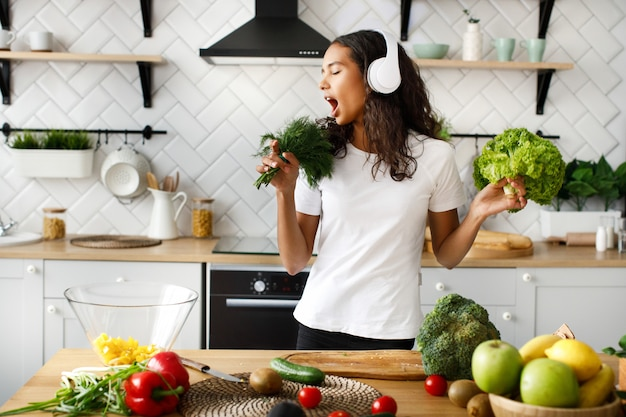 Funny mulatto woman in big wireless headphones is singing on imaginary greenery microphone on the modern kitchen near table full of vegetables and fruits Free Photo