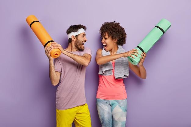 재미 있은 다민족 여자와 남자는 체육관에서 재미를 가지고, 겹쳐서 Karemats와 싸우십시오. 무료 사진